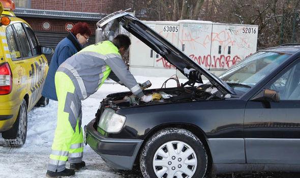 Man Looking At Broken Down Car