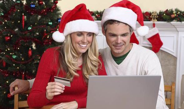Couple shopping online in Christmas hats